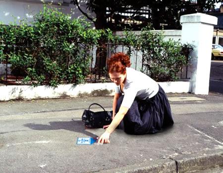 hoteles one, publicidad en la calle mujer recogiendo moneda