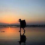 hombre caminando atardecer playa